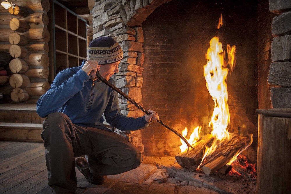 Man inside a log cabin stoking a wood fire