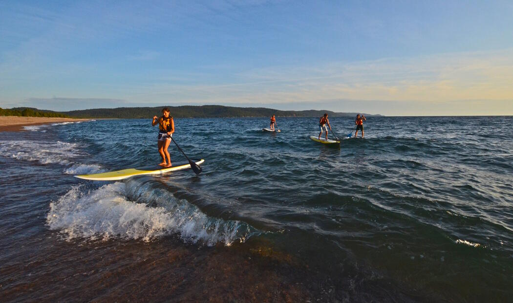 four SUP boards on Lake Superior with beach in background