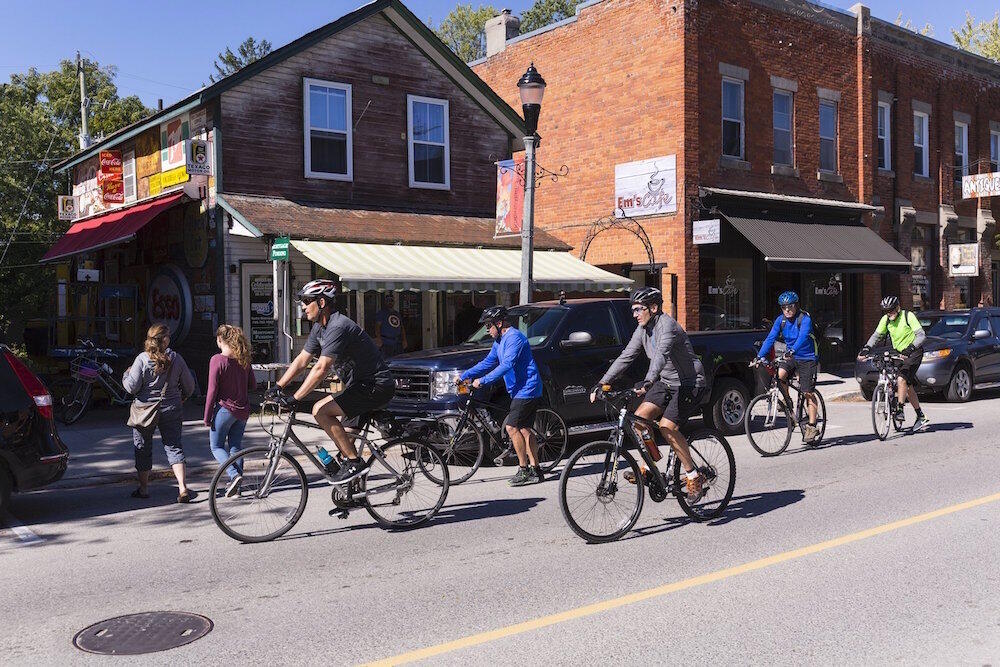 Group of cyclists riding on a town street.