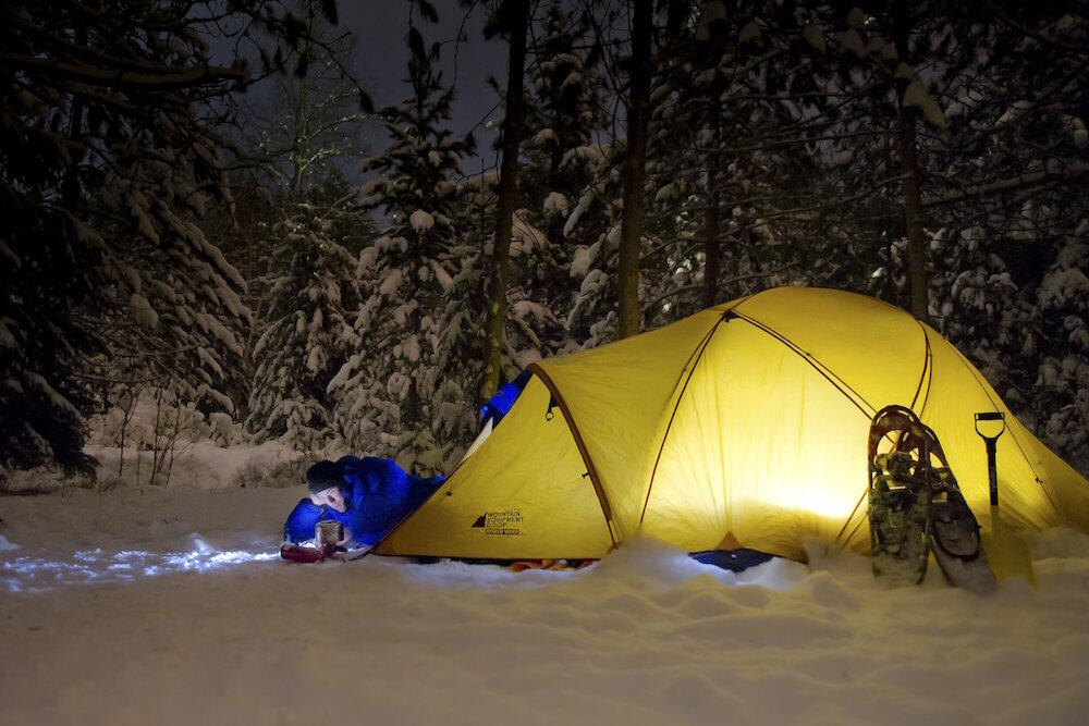 Tent set up in snow with man reading a book.