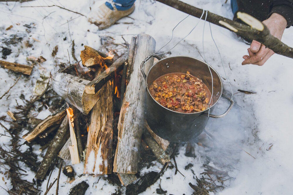 Pot of chili cooking over a fire