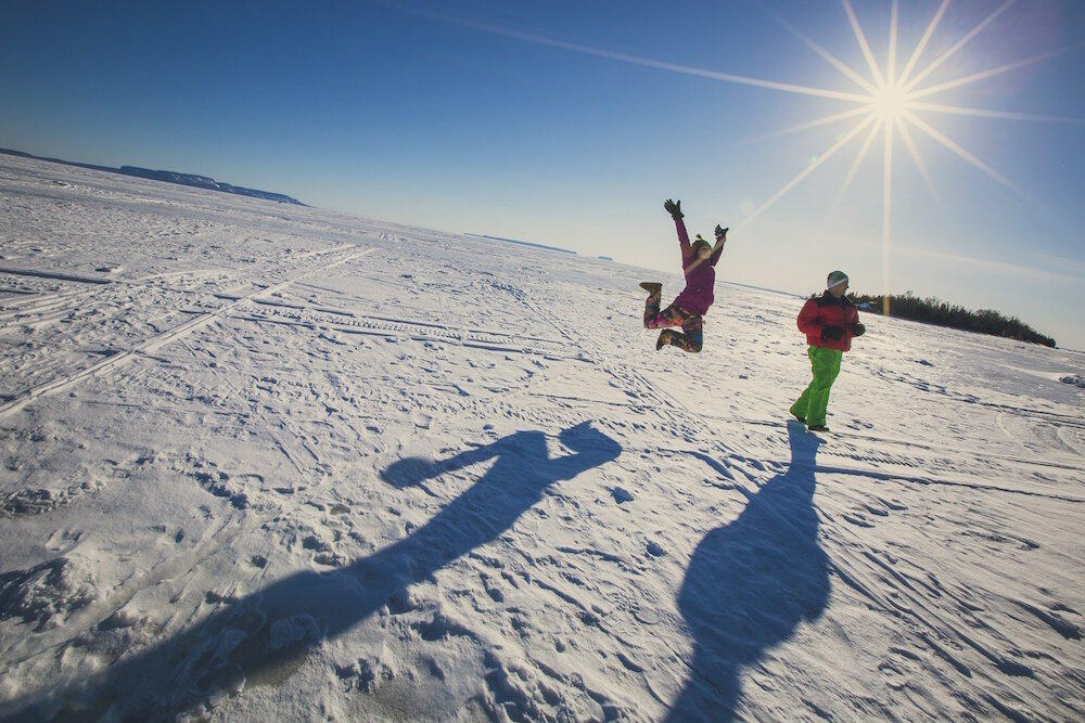 Girl jumping in air on frozen lake.