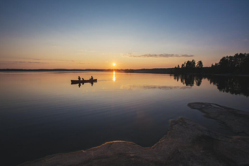 Two people paddling a canoe at sunset on a peaceful lake.