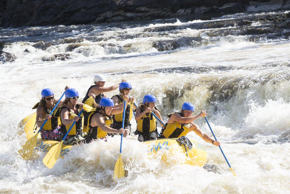 7 people paddling a raft in white water rapids