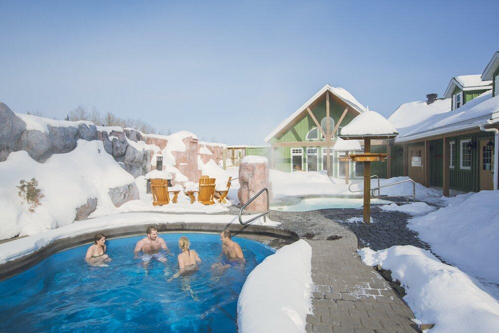 People in a hot tub in the winter at a spa.