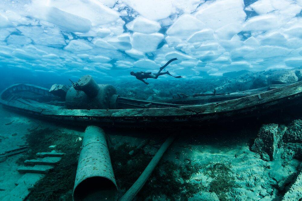 Underwater view of shipwreck with scuba diver
