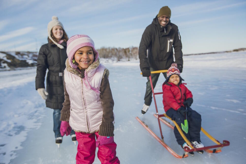 Family of four skating on lake.