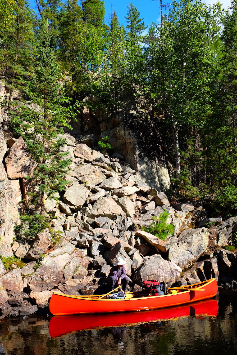 Man in red canoe at base of large boulder portage up a hill