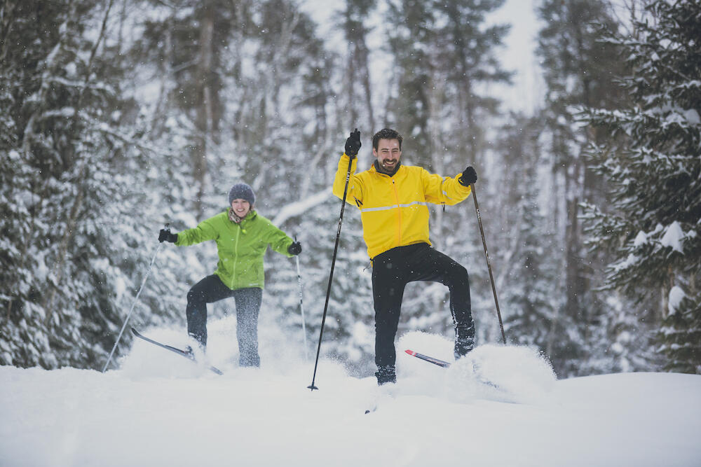 Man and woman skate skiing in powder snow.
