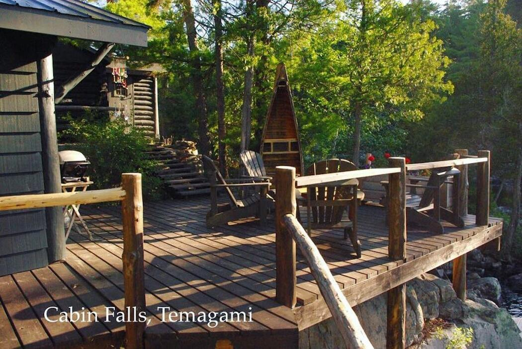 Large wooden deck around a rustic cabin.