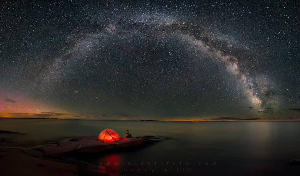 Glowing orange tent in front of the milky way in the night sky.