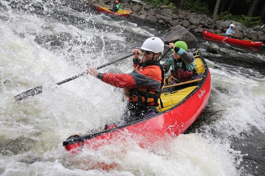 Man paddling a canoe in extreme whitewater.