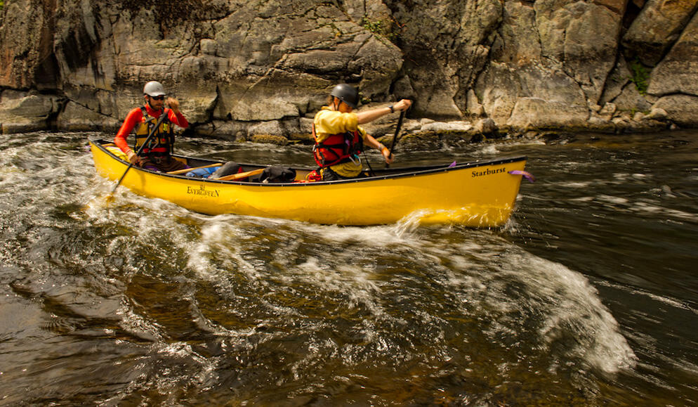 Two canoeists paddling a yellow canoe in whitewater