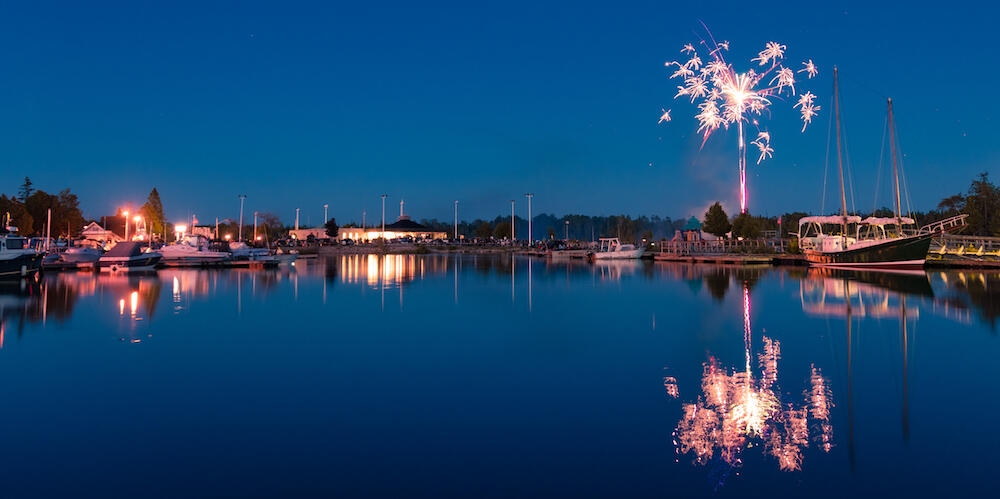 Fireworks in sky over harbour with boats