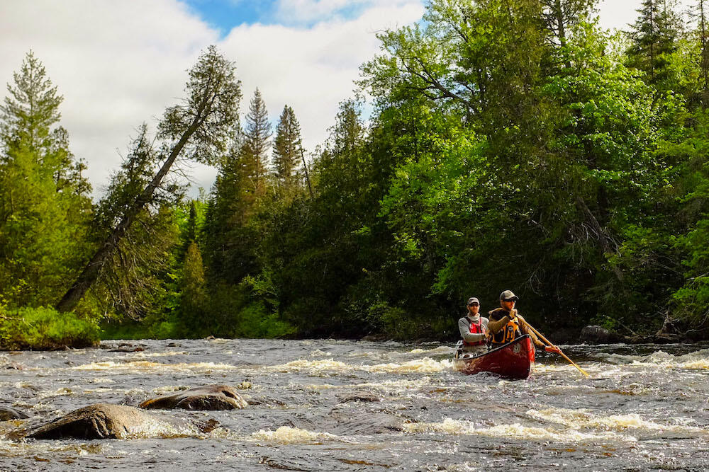 A canoe with two paddlers in minor rapids