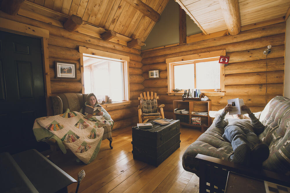 Woman and man relaxing in a cozy log cabin.