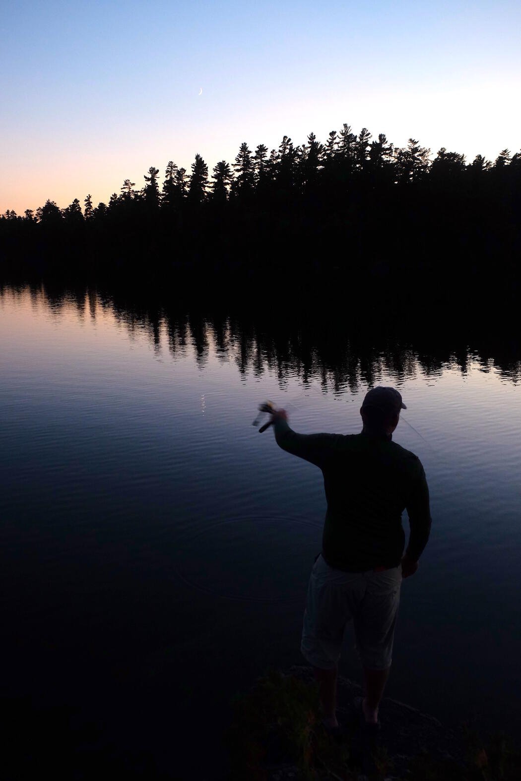 Man fishing during the twilight hours.
