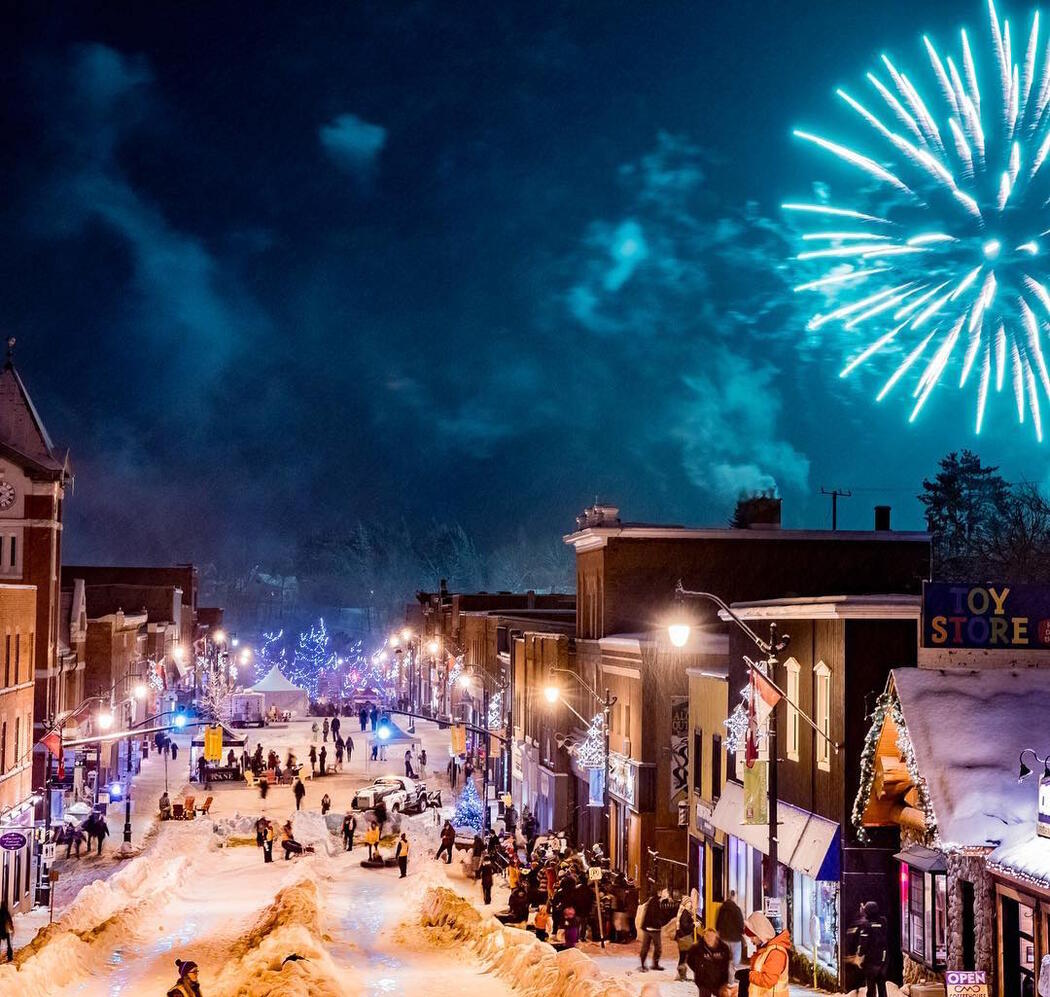 View of people tubing down Bracebridge main street surrounded by historic building.
