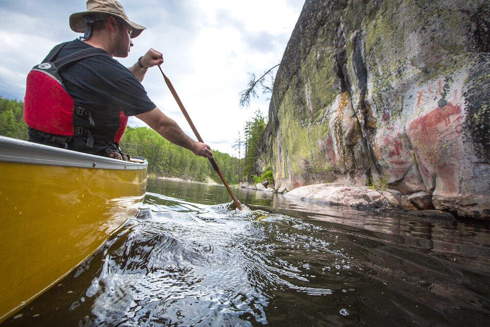 Man in a canoe paddling beside a rock face with pictographs