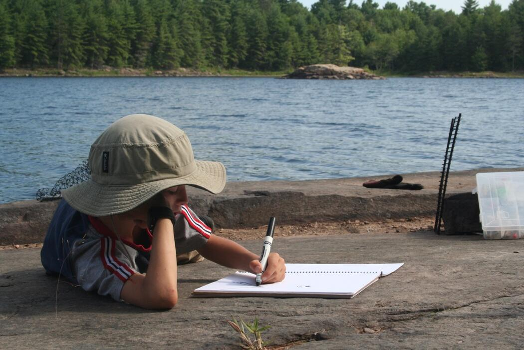 Child writing in a journal while laying on a rock beside a river