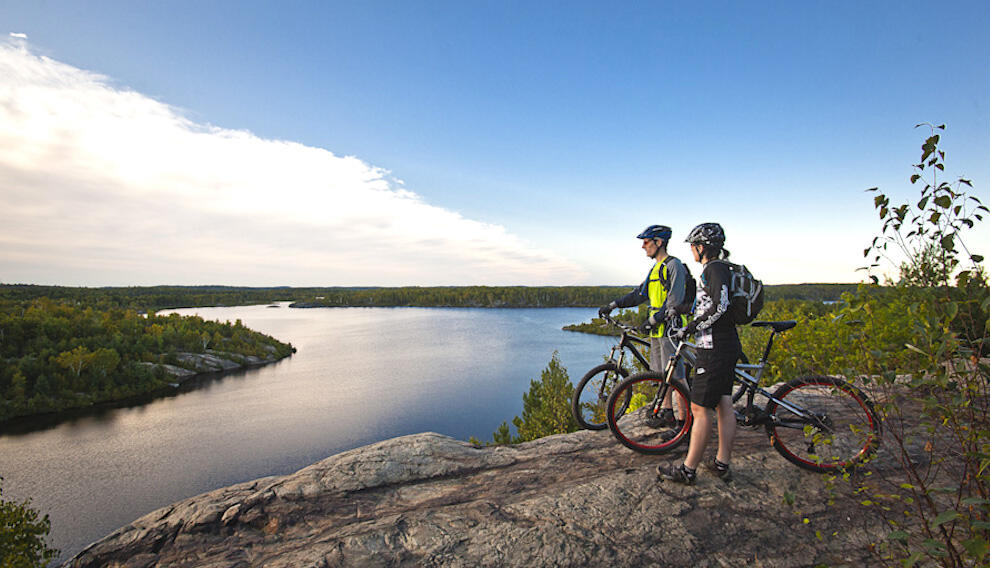 A couple with mountain bikes looking at beautiful view of a lake from top of a cliff