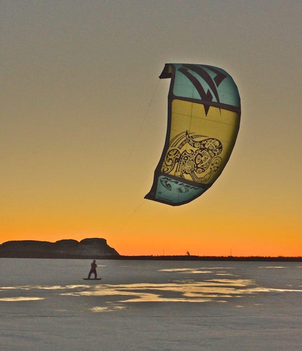 Person on a snowboard snowkiting at sunset