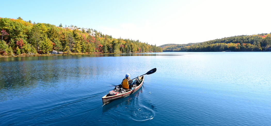 Person paddling solo in a canoe on a beautiful lake in Killarney