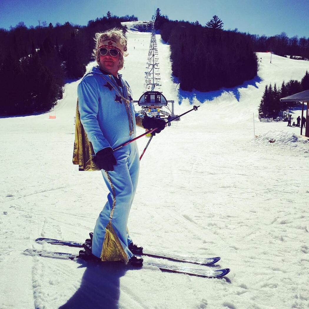Man on skis dressed in power blue outfit with a cape.