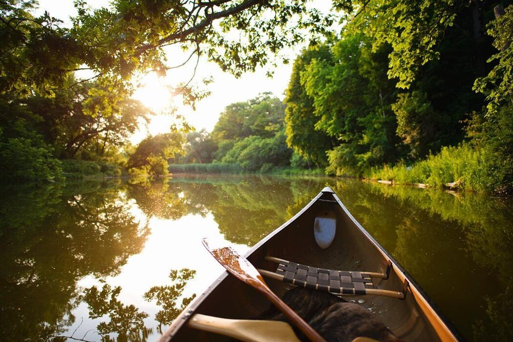 Front of a canoe drifting calming on a river.