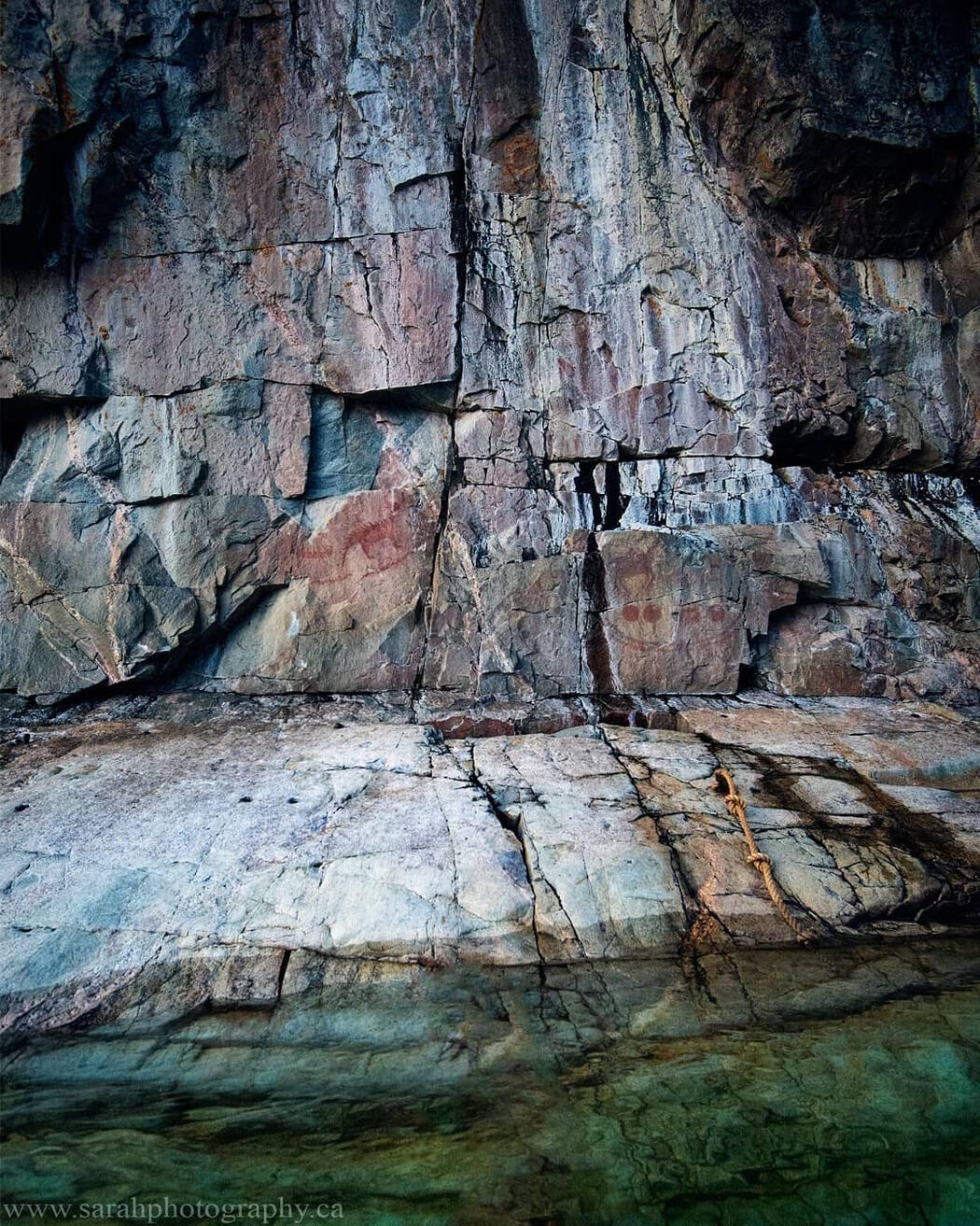 Red pictograph on a vertical rock face.