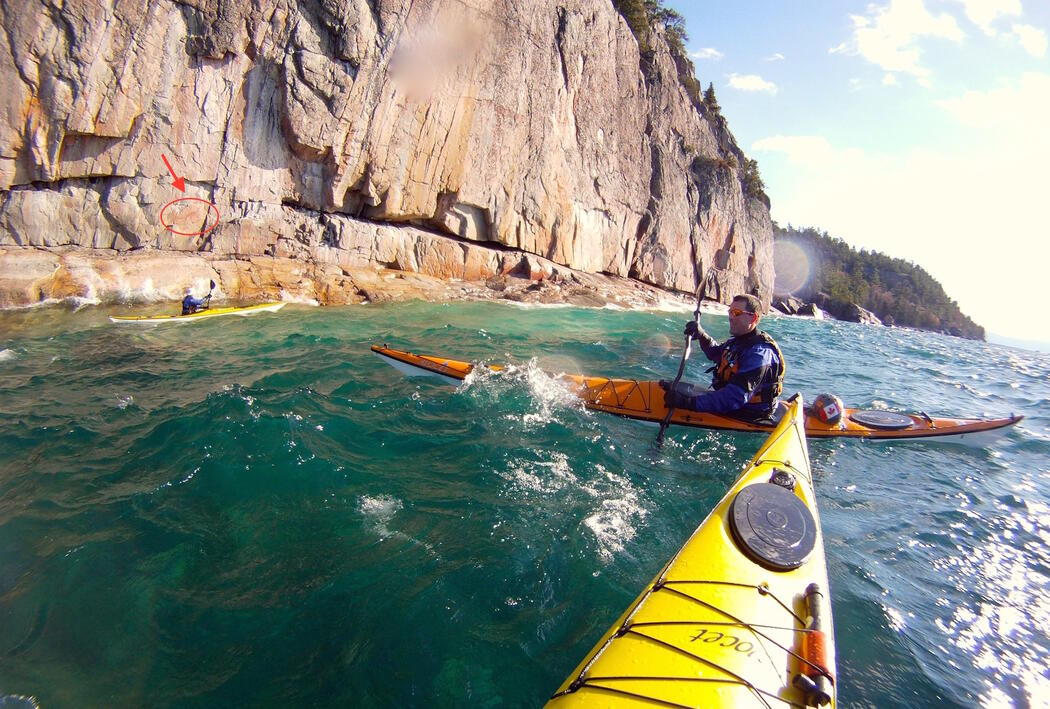 Kayaks paddling in waves, trying to view pictographs.