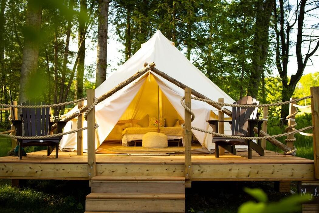 Canvas tent on a wooden platform with 2 chairs on platform.