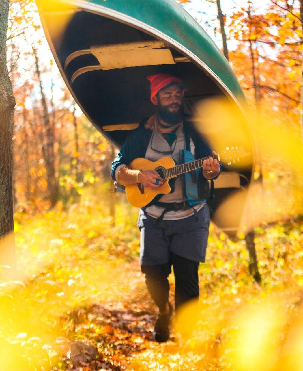 Man strumming on a guitar while portaging a green canoe on his head.