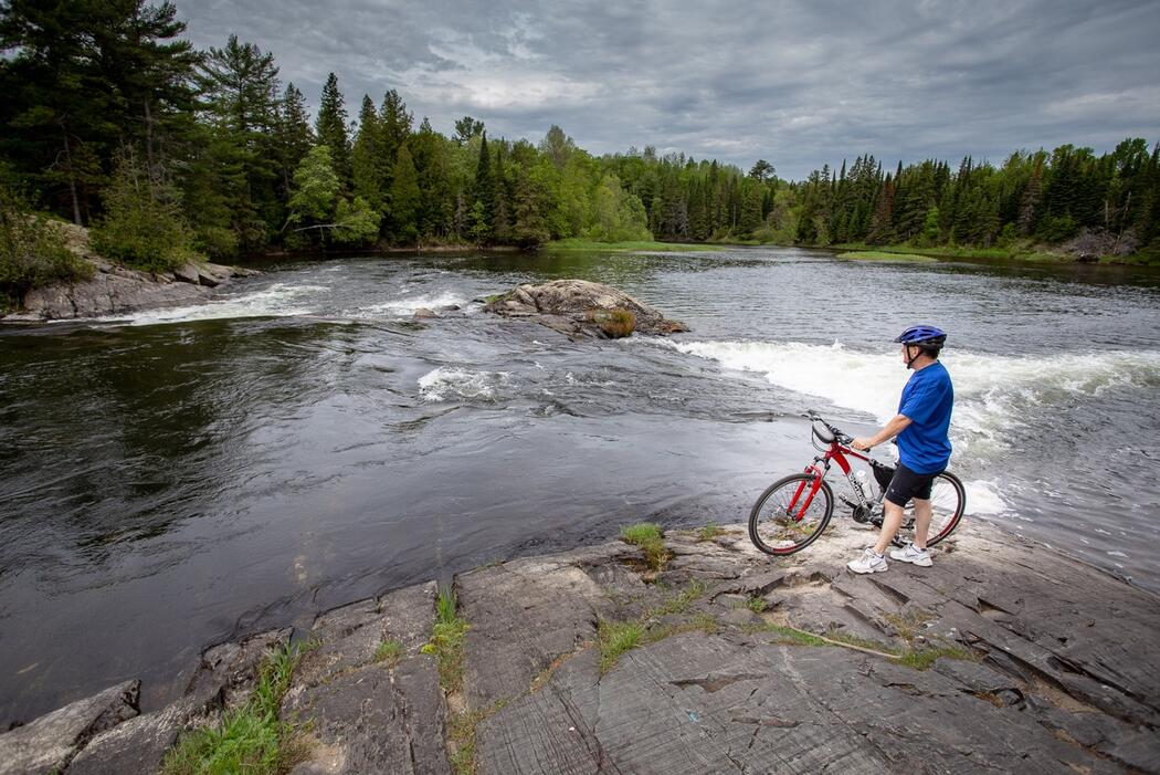 Cyclist standing beside bike beside a beautiful river