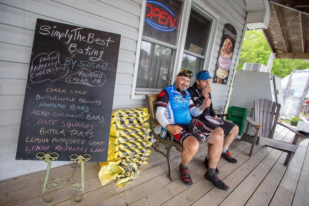 Two male cyclists sitting on a bench in front of a bakery