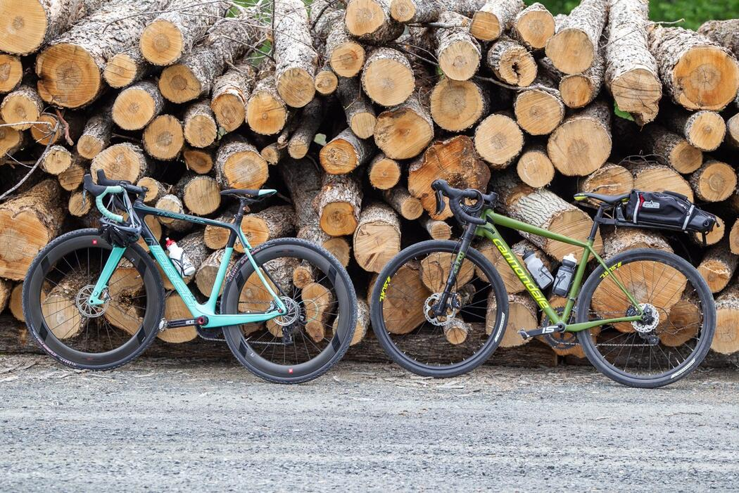 Two bikes leaning against a wood pile