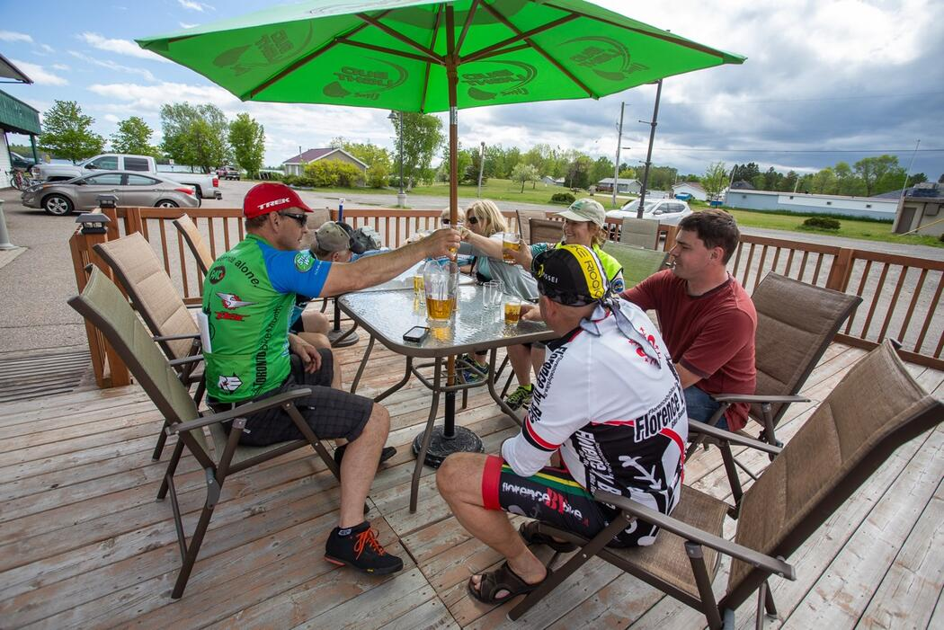 A group of cyclists enjoying food and drinks on a patio