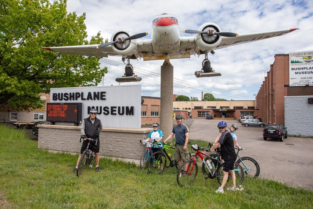 Four cyclists standing with bikes in front of Bushplane Museum