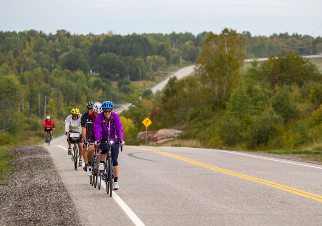 Group of cyclists riding in single file on shoulder of paved road.
