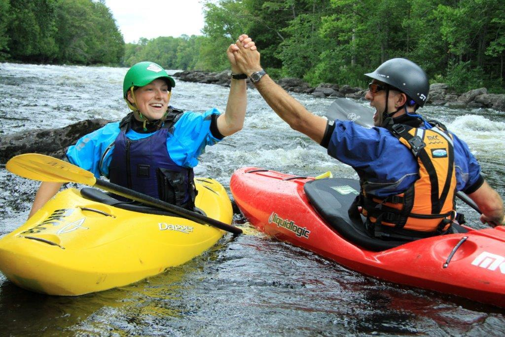 Two people in whitewater kayaks smiling and high-fiving.