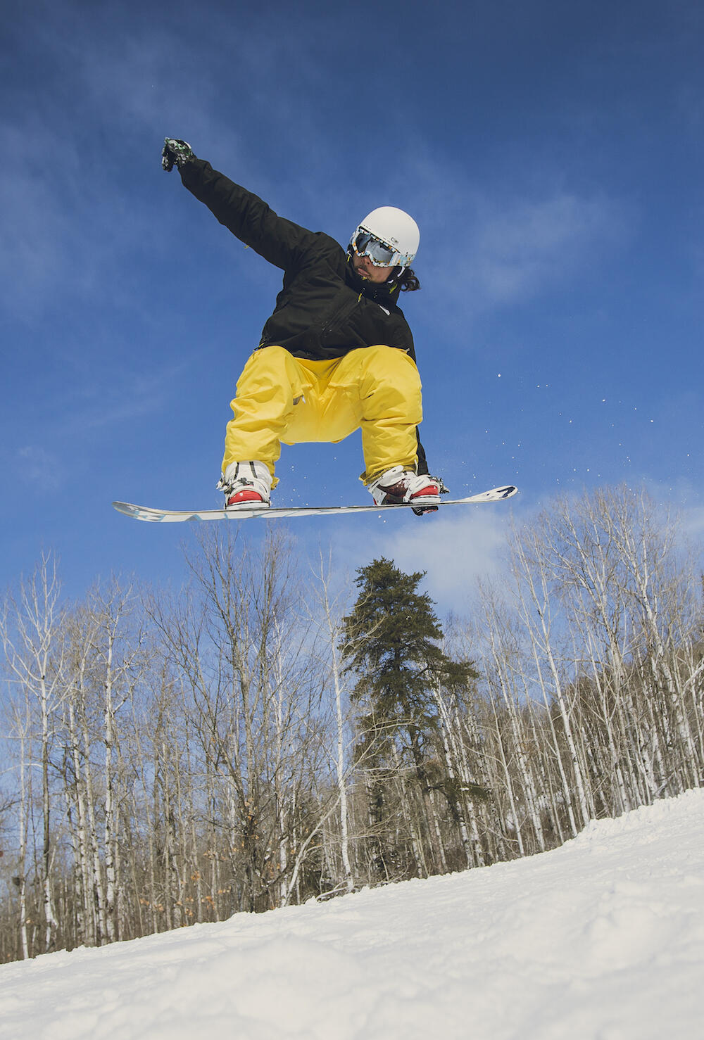 Young man catching some air on a snowboard.