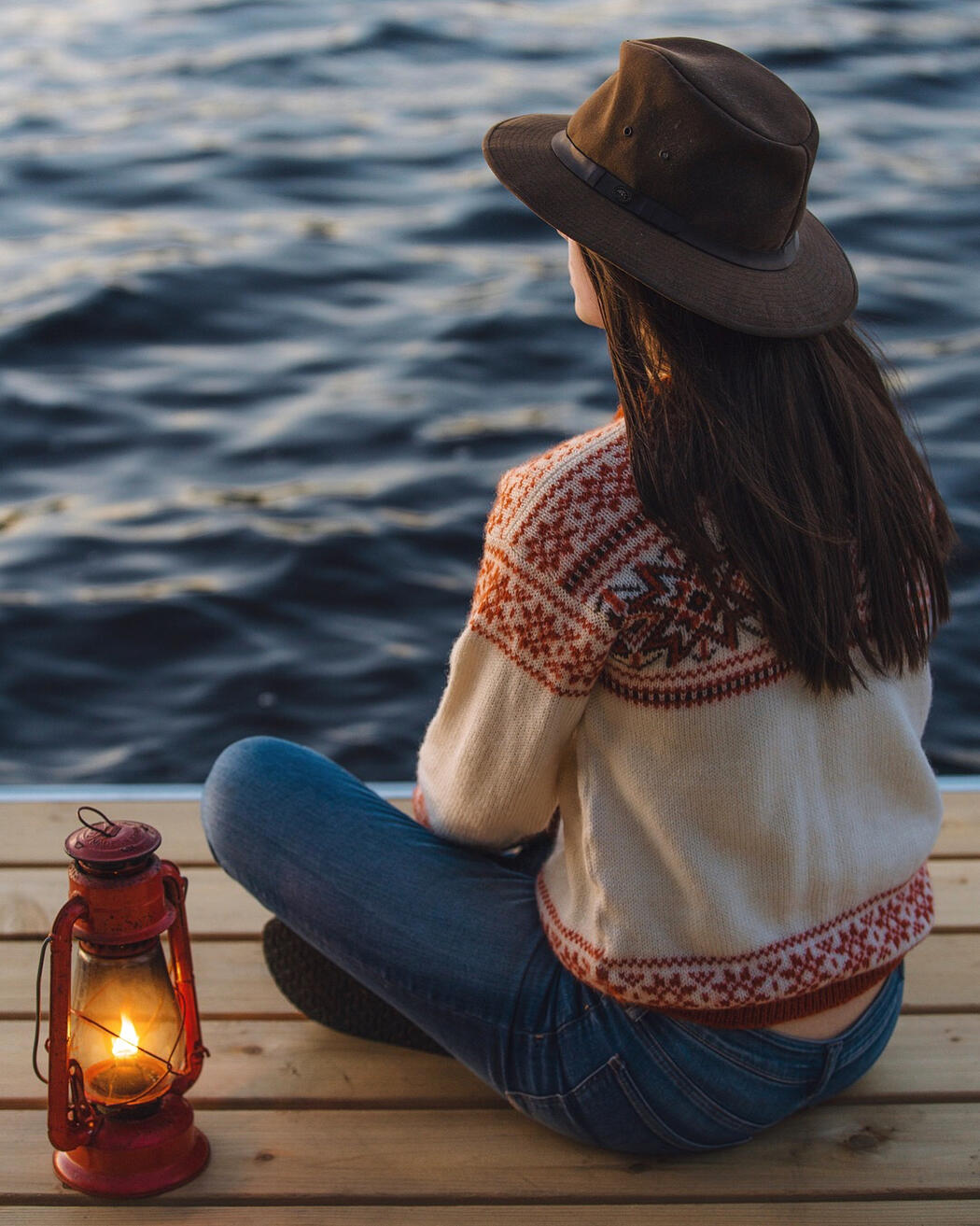 Young woman  with a brimmed hat sitting on a dock beside an old-fashioned lantern.
