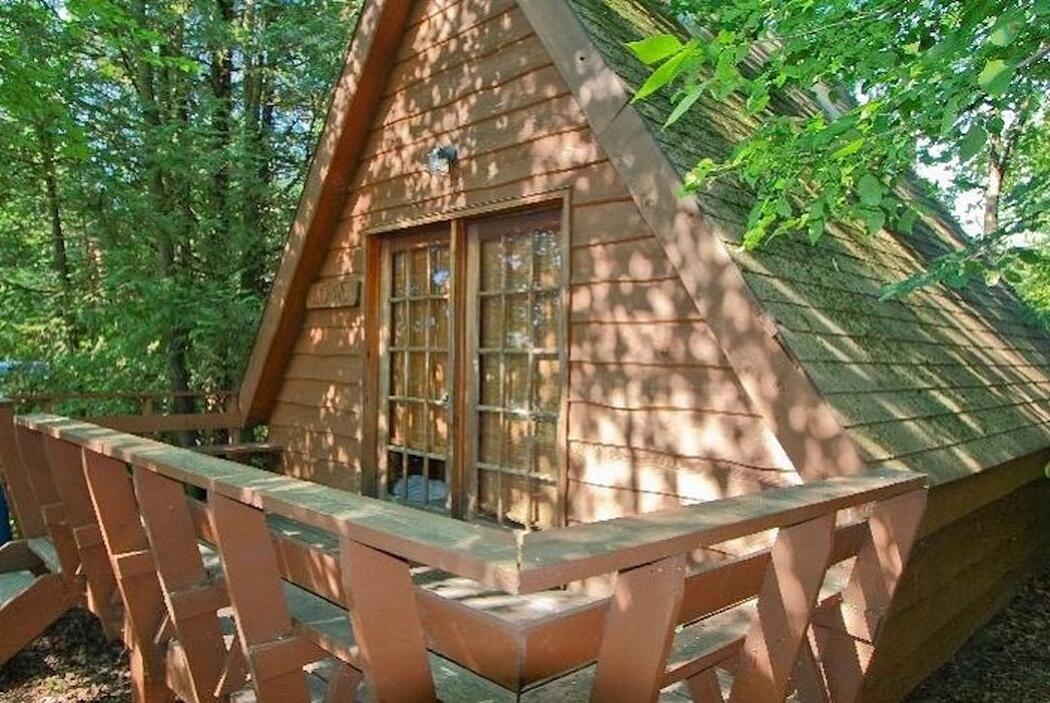 Small A-frame cabin with deck.