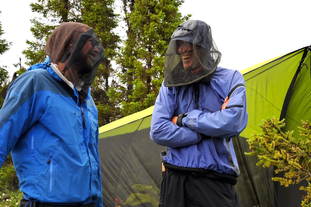 Two men in bug jackets talking in front of a tent.