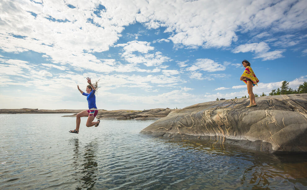 Woman jumping off rock into the water