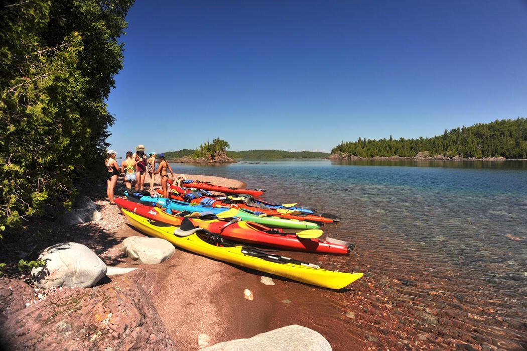 A group of kayaks and kayakers on the shore of Lake Superior.