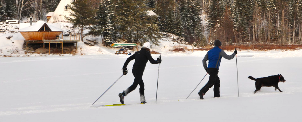 Two people cross country skiing on a lake in front of a yurt.
