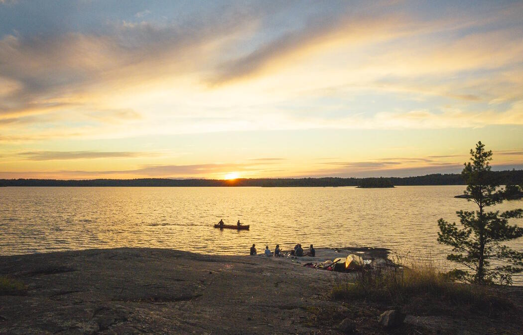 Group relaxing on smooth rocky shore at sunset. Canoe paddling by.