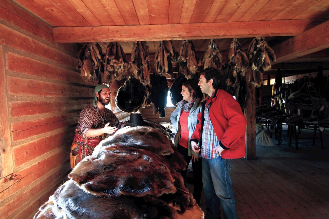 People looking at pile of furs in a log cabin.