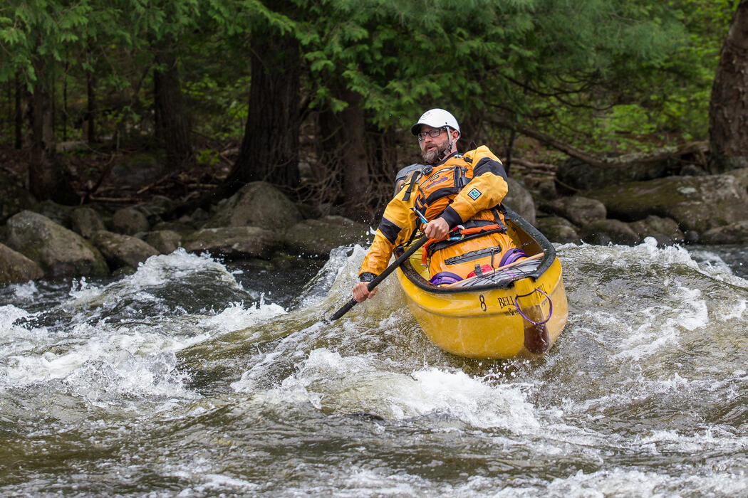 Man paddling a yellow canoe in whitewater
